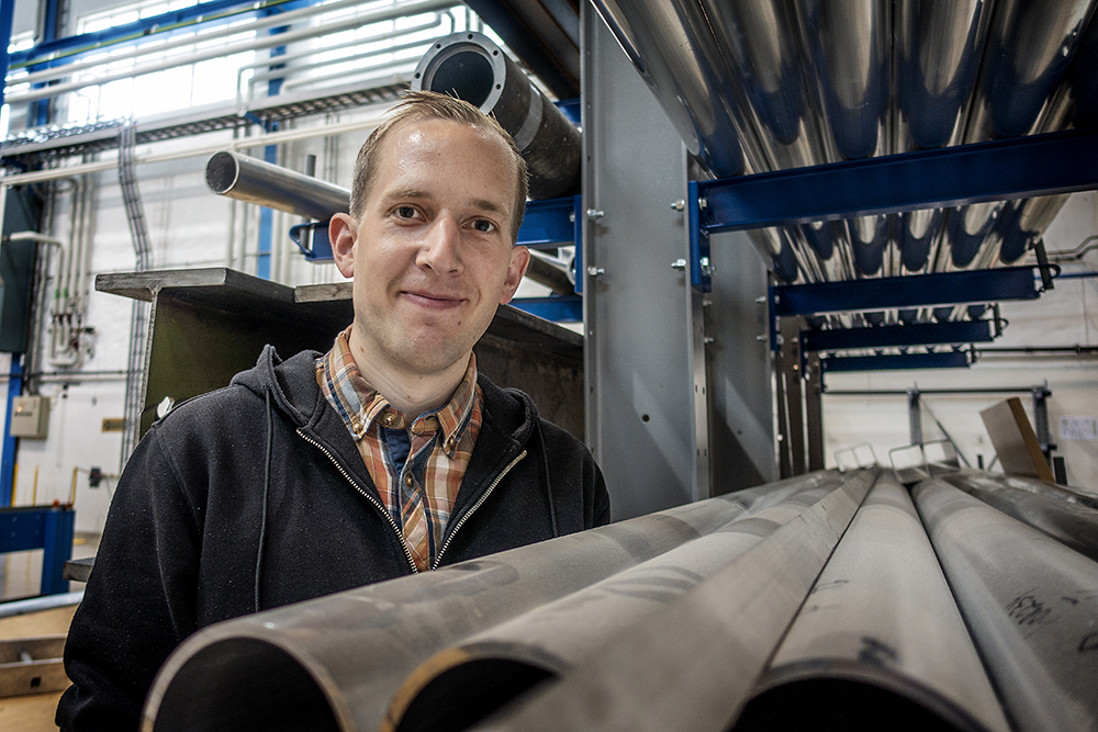 PhD Candidate Bjørn Håkon Frodal in the lab surrounded by aluminium profiles