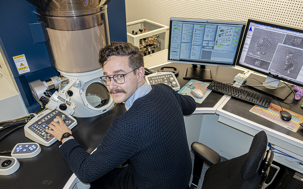 Emil Christiansen at the desk in front of the supermicroscope TEM at NTNU.