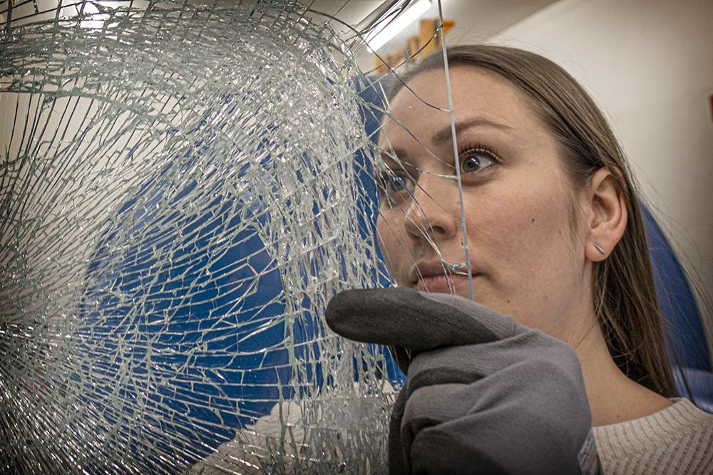 Karoline Osnes wit a laminated glass plate full of cracks after a balst