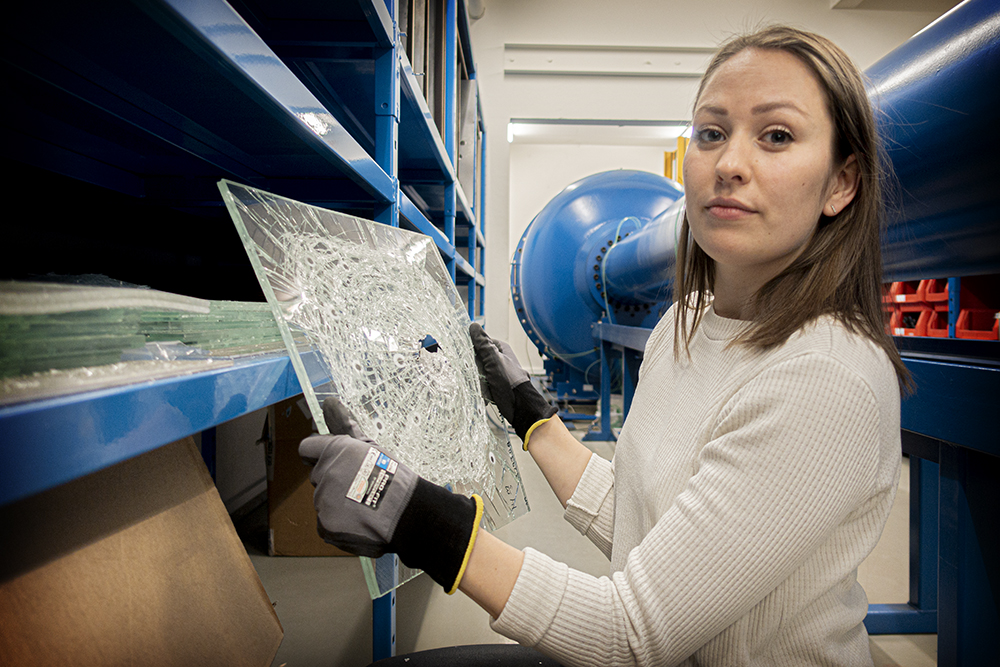 Karoline Osnes showing fractured glass plate. The shock tube in the background