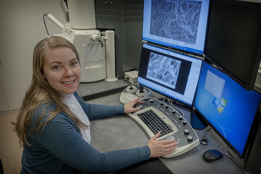 Susanne Thomesen in front of screens showing microstructures in aluminium