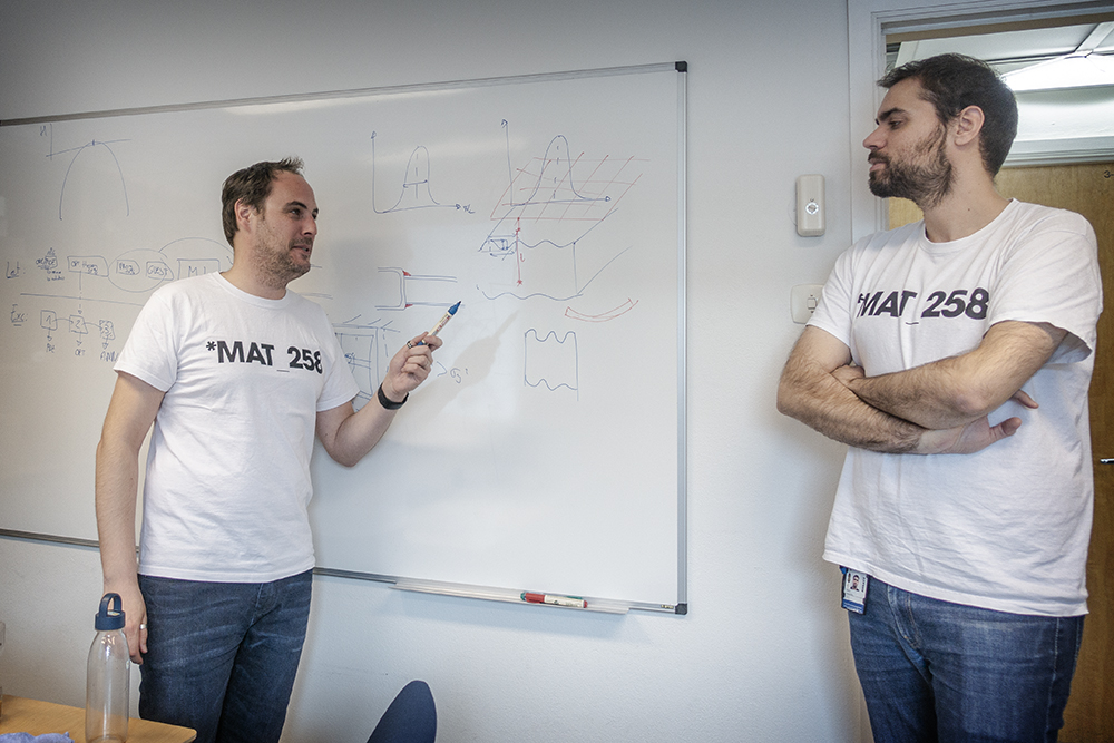 Two men in similiar T-shirts in front of a whiteboard